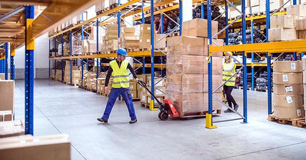 Gestione magazzino e facchinaggio - uomo trasporta pacchi su transpallet in un magazzino